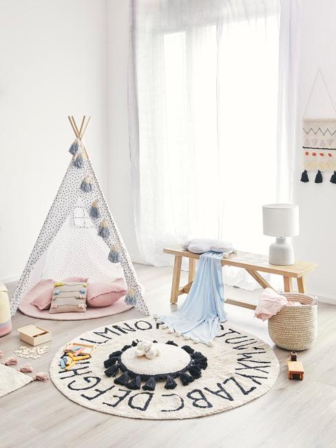 Muurdecoratie babykamer: een grijze tipi met roze kussens en rond vloerkleed naast houten zitbank met tafellamp