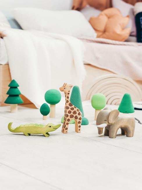 Houten speelgoed op wit vloerkleed naast een bed