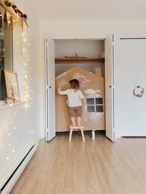 Meisje dat een handgemaakt kartonnen huis schildert