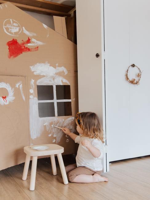 Peuter schildert op karton in babykamer in wit