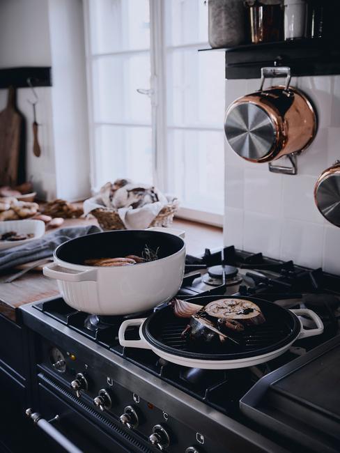 Messing keukenaccesoires over de pannen