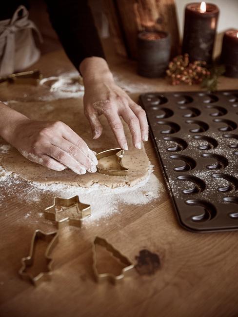 Kersthapjes uit de oven van ovenschaal met vormen op houten tafel