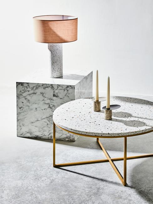 Terrazzo: marmeren bijzettafel met tafellamp naast marmeren salontafel met goudkleurige poten en kandelaar