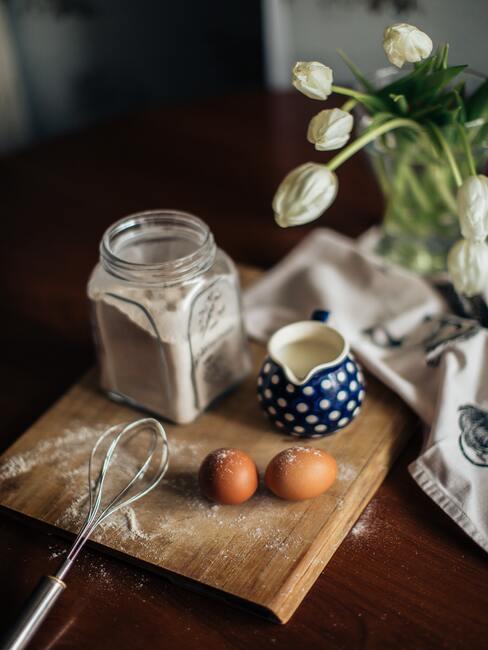 Bloem, melk en eieren op een houten snijplank