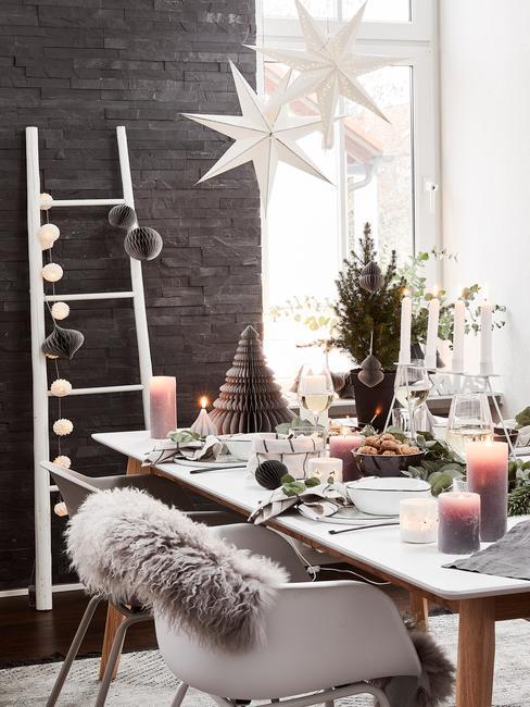 Kerst ontbijt ideeën: gedekte tafel met zilverkleurige serviesset en kaarsen op tafel, stoelen met schapenvacht en verschillende kerstdecoraties