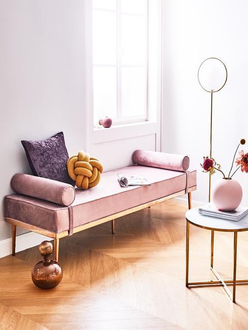 Velvet: fluwelen zitbank met paars fluwelen sierkussen en goudkleurige salontafel met roze vaas met bloemen