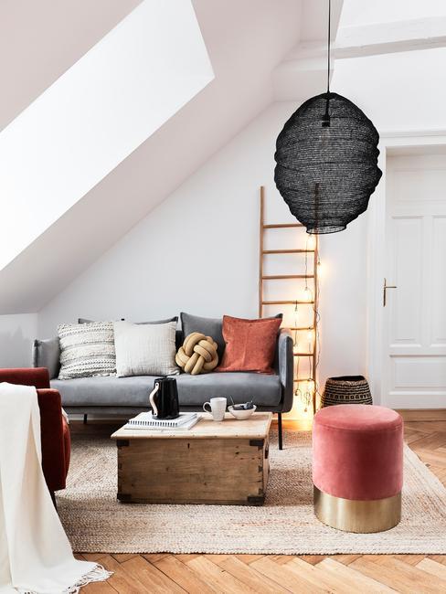 Grijze zitbank met sierkussens naast een houten salontafel, fluwelen kruk en zwarte hanglamp