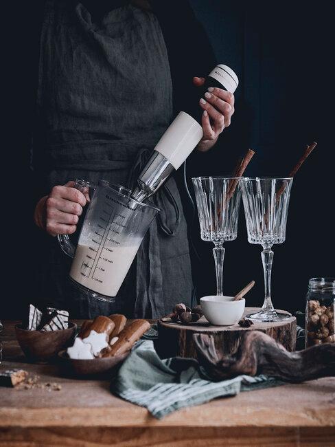 Keuken voorgerechten kerst in kristallen wijnglazen met chefkok in grijze koksbuis op houten tafel