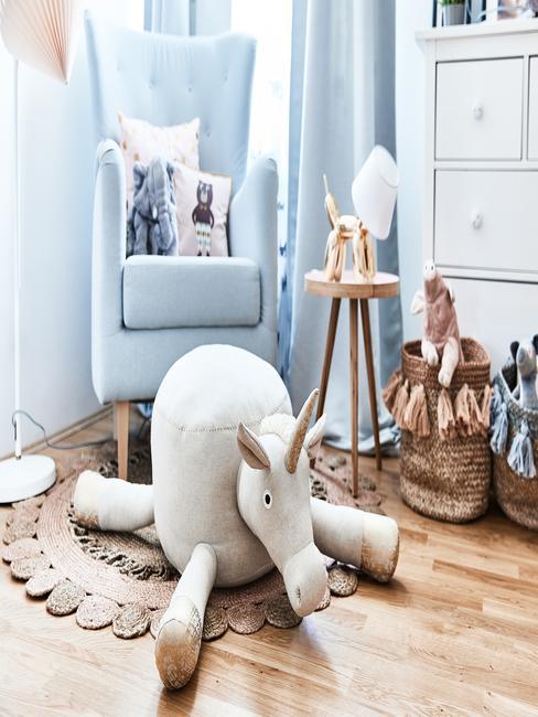 Peuterkamer: blauwe fauteuil met sierkussens in wit naast een houten bijzettafel