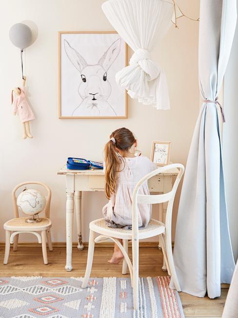 Peuterkamer: klein meisje, zittend aan een wit bureau op een witte stoel