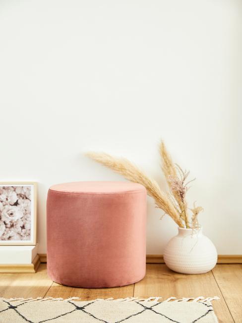 Roze fluwelen poef naast een witte vaas