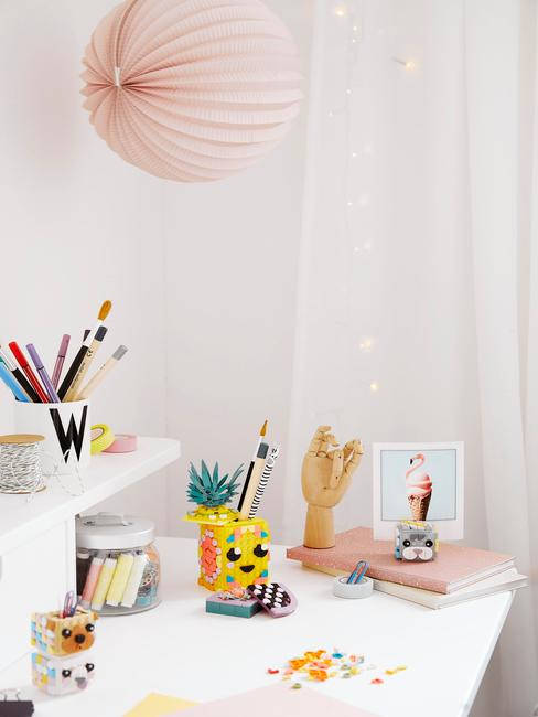 Een wit bureau met veel kleurrijke schrijf- en tekenaccessoires
