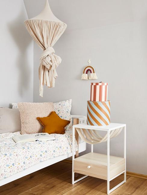 Wit beddengoed met een stippenpatroon en kussens naast een wit nachtkastje met dozen