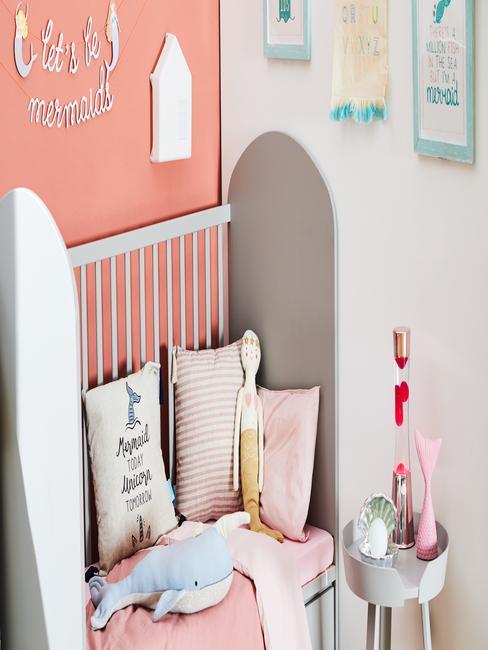 Grijze kinderbed met sierkussens in wit en roze