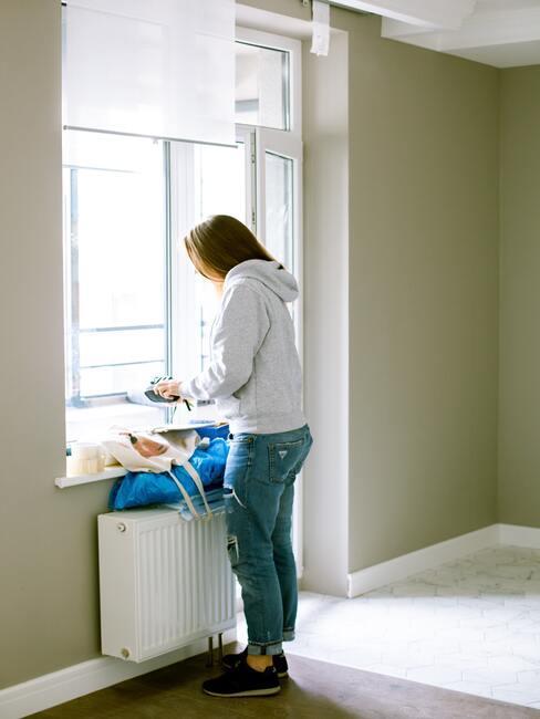 De vrouw ruimt na het schilderen de kamer op