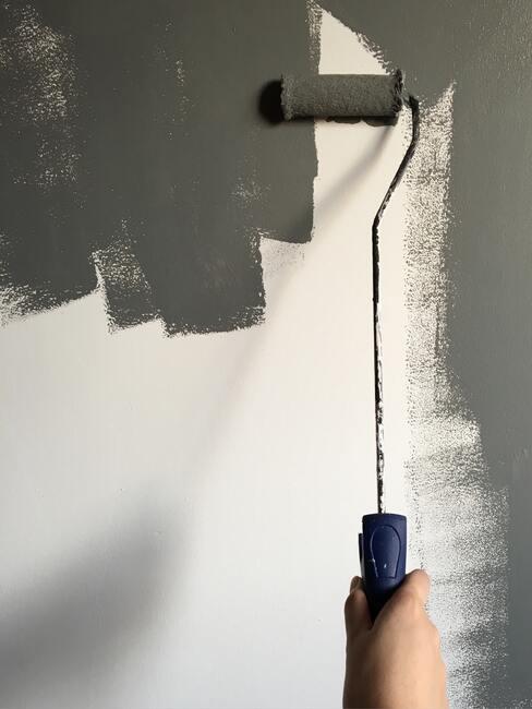 Verf de muur grijs met een roller