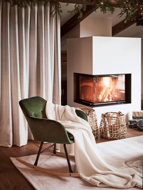 Woonkamer met openhaard en groene velvet schommelstoel