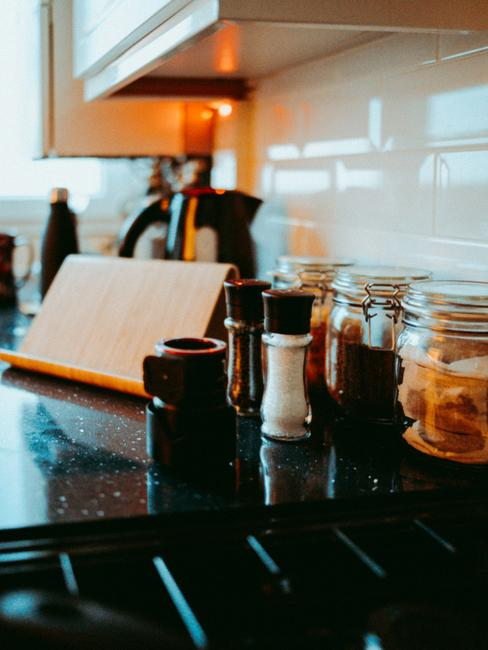 Metalen zoutvaatje op een houten tafel en glazen opbergpotten
