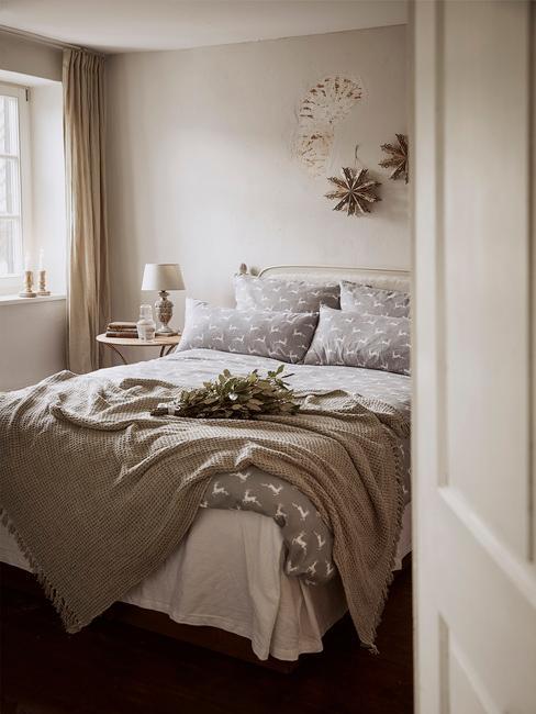 Kerstfilms: een beige slaapkamer met grijs beddengoed en kerstversiering