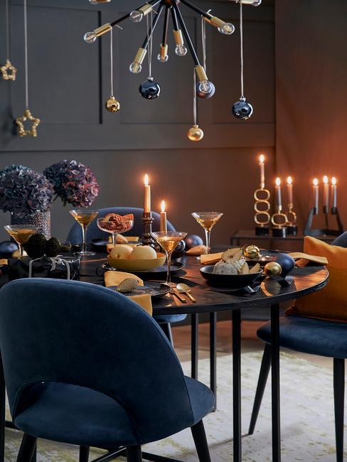 Kerstdecoratie in een marineblauwe woonkamer met blauwe stoelen en een zwarte tafel