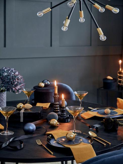 Gedekte tafel in blauw en goud kleur met kaarsen en gele servetten