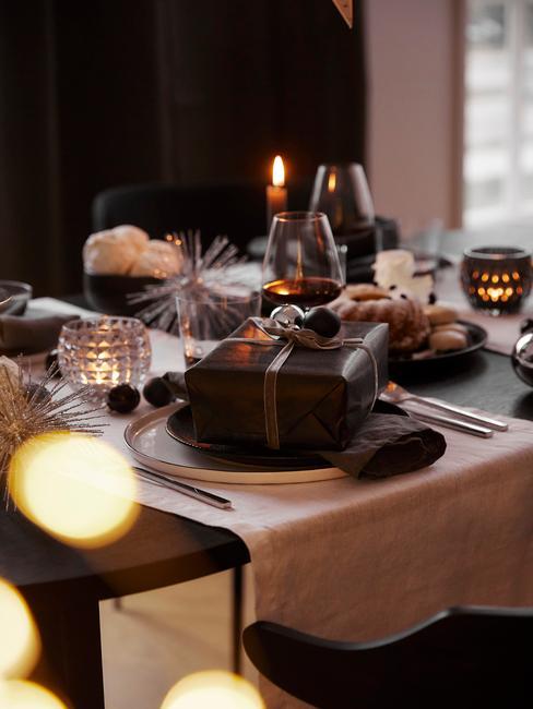 Gedekte tafel met serviesset, witte tafelloper en cadeau
