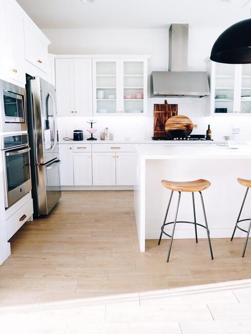 Keuken in wit met houten barkrukken en moderne kookaccessoires