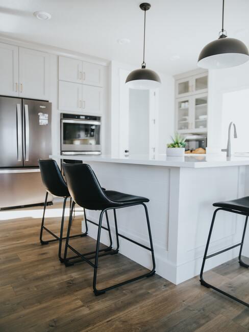 Wit kookeiland naast zwarte barkrukken in scandi stijl keuken