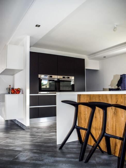 Keuken in zwart en wit met houten elementen en zwarte barkrukken