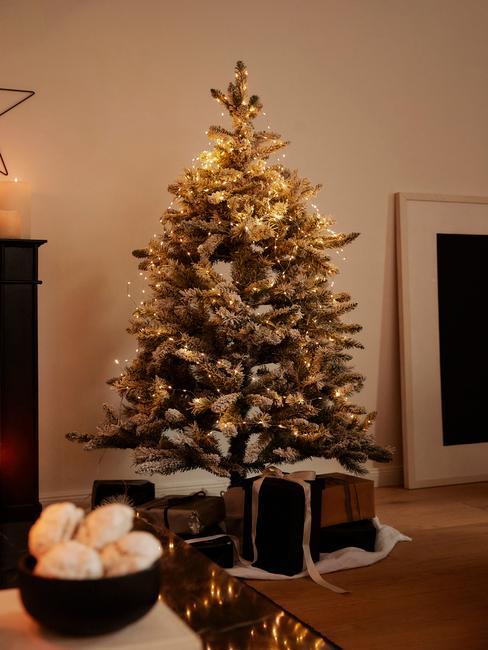 Kerstboom met verlichting en kerstversiering in de woonkamer