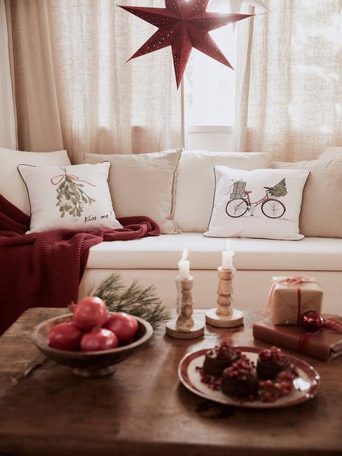 Kerstdecoratie van de woonkamer in wit en rood met kaarsen en sierkussens