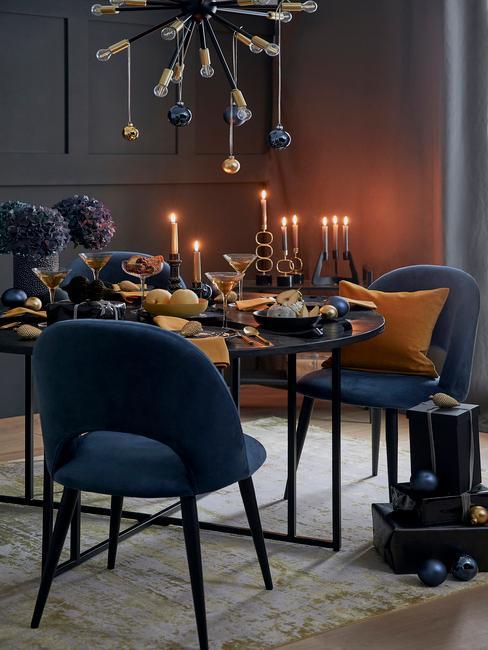 Blauwe stoelen en zwarte, gedekte tafel met serviesset en besteksset in goud kleur en gele servetten