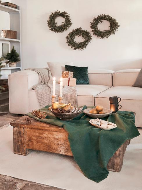 Woonkamer in het wit met een comfortabele bank en sierkussens en een witte salontafel met kaarsen en kerstversiering