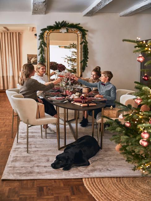Kerstboom naast een eetfafel met familie