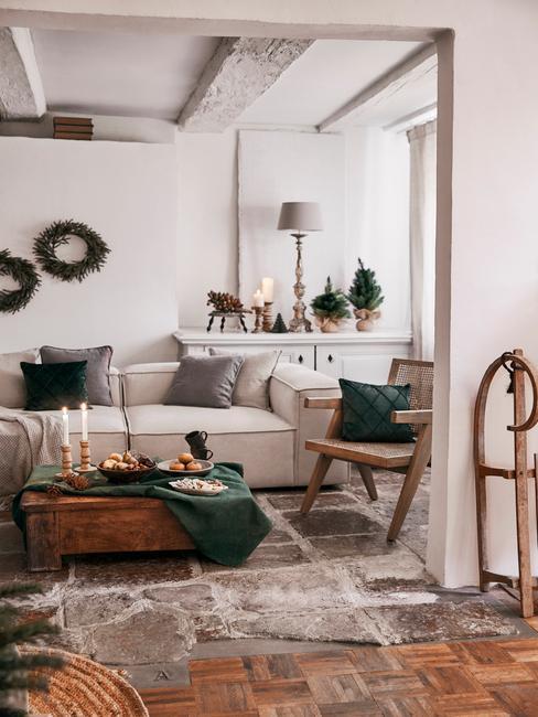 Dobbelspel kerst: woonkamer in het wit met een comfortabele bank en sierkussens en een witte salontafel met kaarsen en kerstversiering