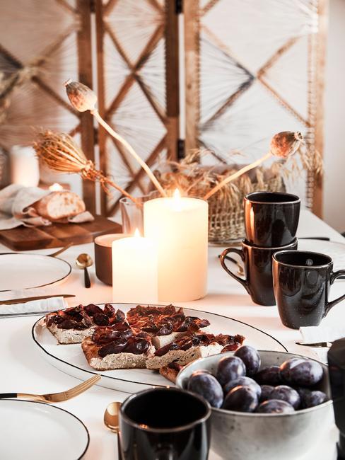 Gedekte tafel met serviesset en bloemen en tafeldecoratie landelijk