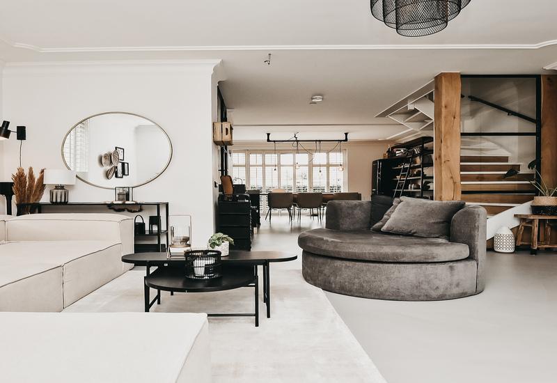 huiskamer met witte lenon sofa en grijs rond daybed met zwarte bijzettafel