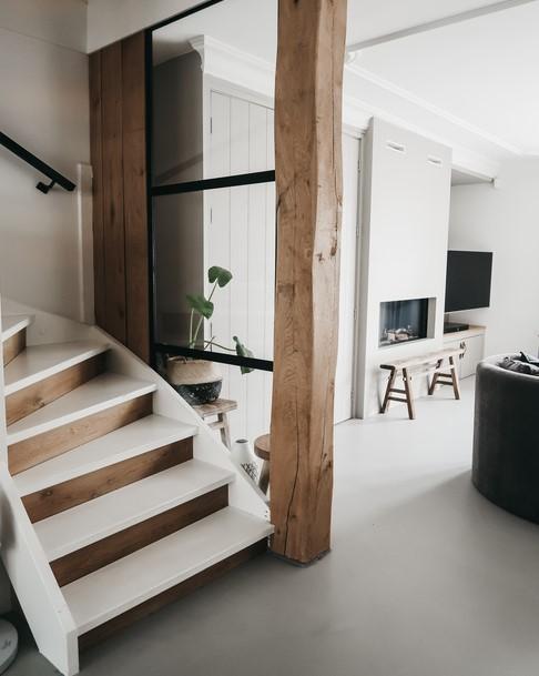Zwart stalen deur en houten trap in huis van manon tilstra