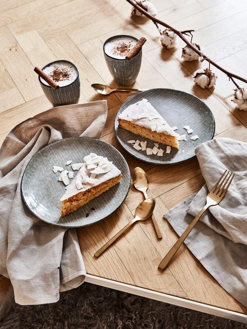 Serviesset in grijs op houten tafel met bestekset in goud kleur en grijze servetten