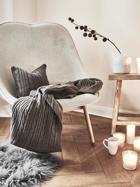 Comfortabele fauteuil in wit met sierkussen en plaid in grijs naast een houten bijzettafel met kaarsen