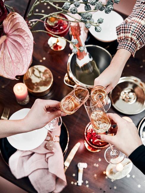Oudejaarsavond feest met vrienden thuis proosten met roze procecco