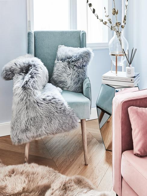 Woonkamer meubels: fauteuil in blauw met zachte plain van schapenvacht in grijs