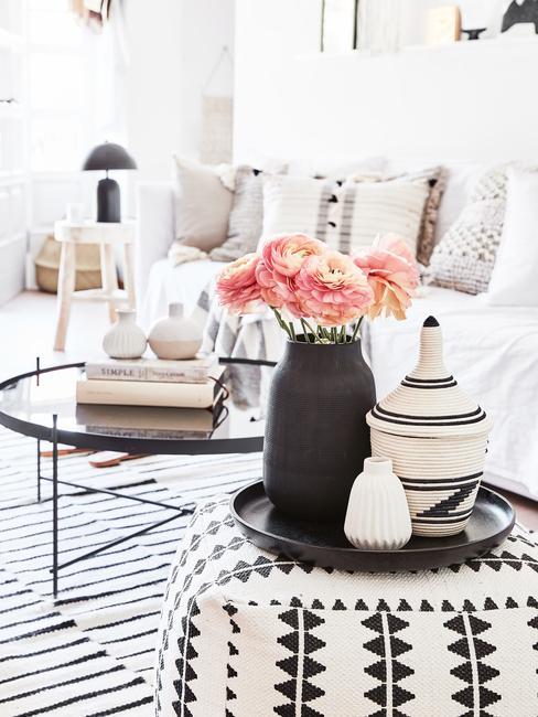 Zwarte vaas met bloemen op dienblad