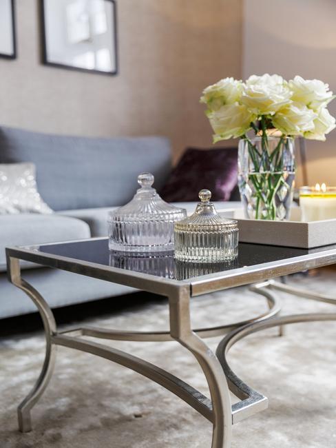Grote woonkamer met metalen salontafel met glazen blad en bloemen in vaas