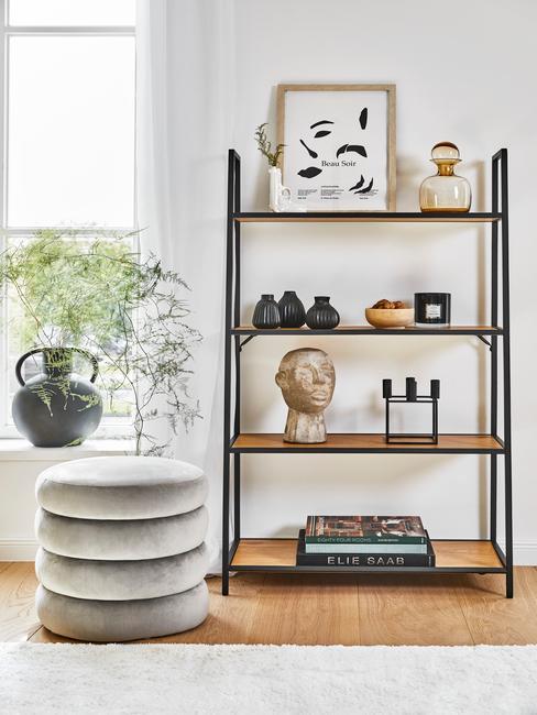 wandkast met decoratieve acessoires en ronde grijze poef