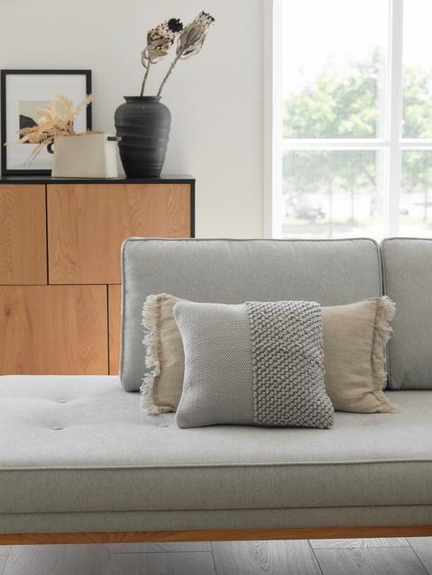 Grijze bank in woonkamer met decoratieve kussens