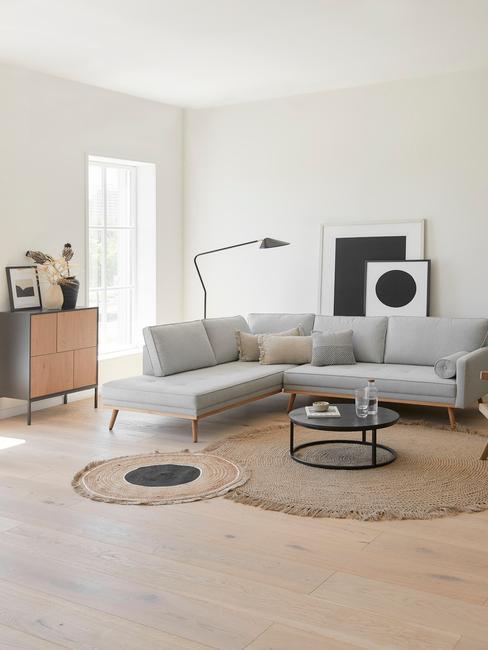 woonkamer met grijze hoekbank, zwarte vloerlamp, rotan vloerkleden en zwarte salontafel
