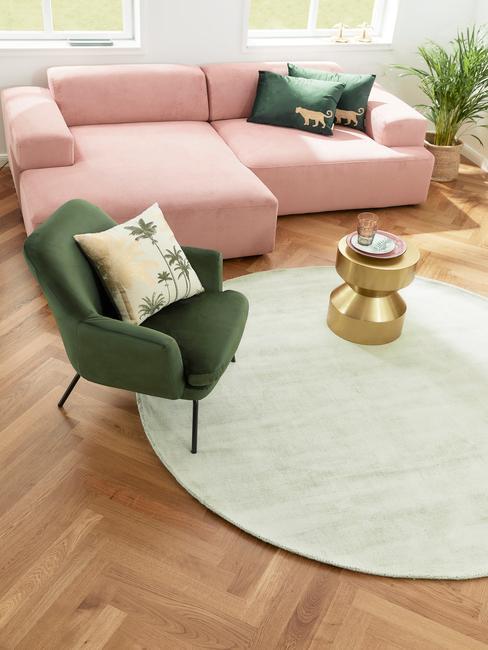 Grote woonkamer met roze bank en groene feateuil