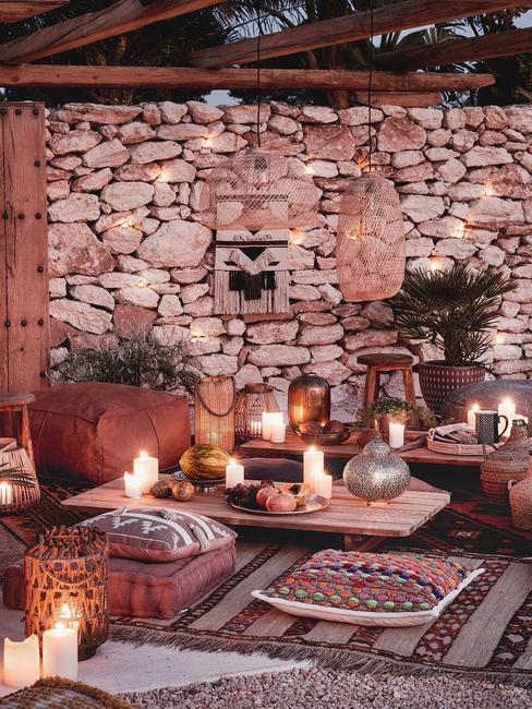 Taras w stylu orientalnym z dużą ilością świec, dywanami i poduszkami na ziemi