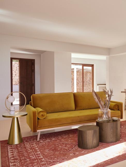 Salon w stylu boho z sofą w kolorze ochry i drewnianymi dodatkami
